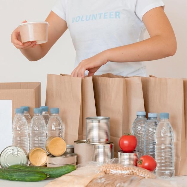 Volontari mettendo cibo cotto e acqua per la donazione in borsa Foto Gratuite