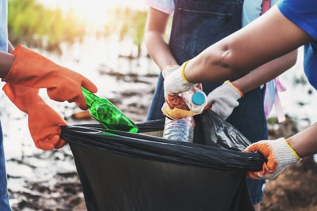 Volunteer woman picking up garbage plastic for cleaning at
