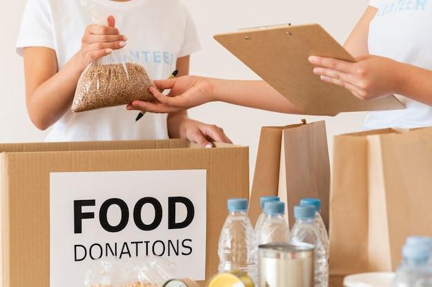 Volontari che controllano il cibo per la donazione con il blocco note Foto Gratuite
