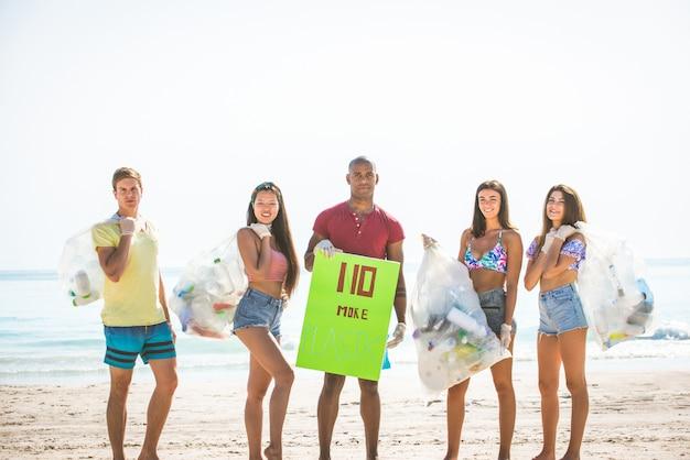 ビーチでプラスチックを収集するボランティア Premium写真