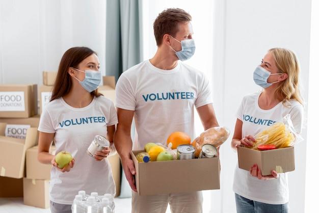 Волонтеры держат коробки для пожертвований еды Premium Фотографии