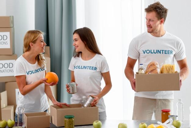 Volontari che preparano scatole con disposizioni per beneficenza Foto Gratuite