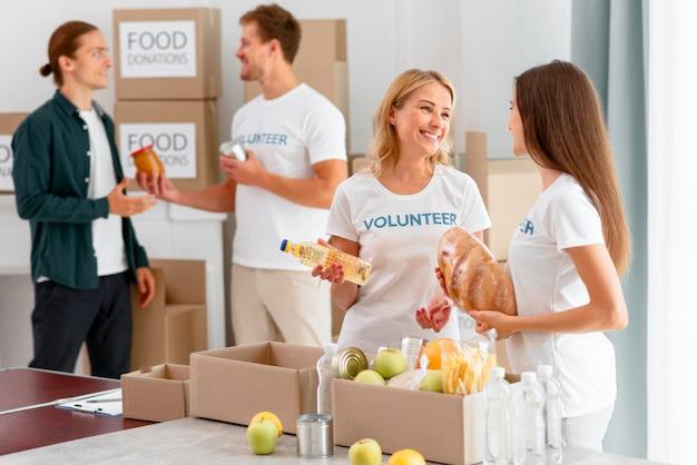 Volontari che preparano provviste di cibo per la donazione Foto Gratuite