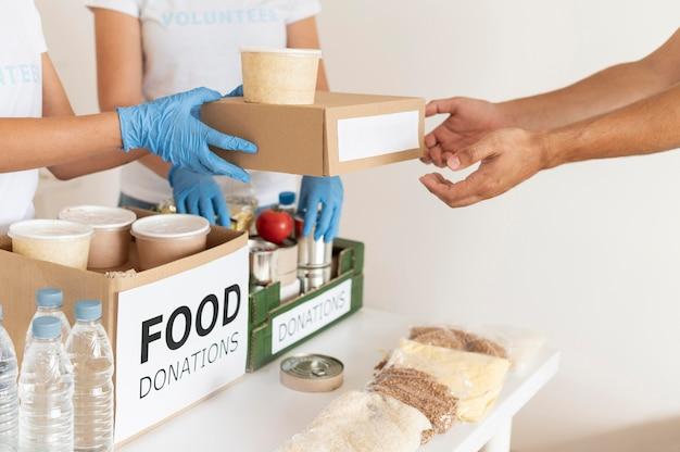 Volontari con guanti che consegnano scatole con provviste per la donazione Foto Gratuite