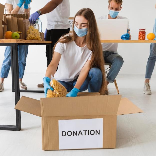 Волонтеры в медицинских масках и перчатках готовят ящики для пожертвований с провизией Бесплатные Фотографии