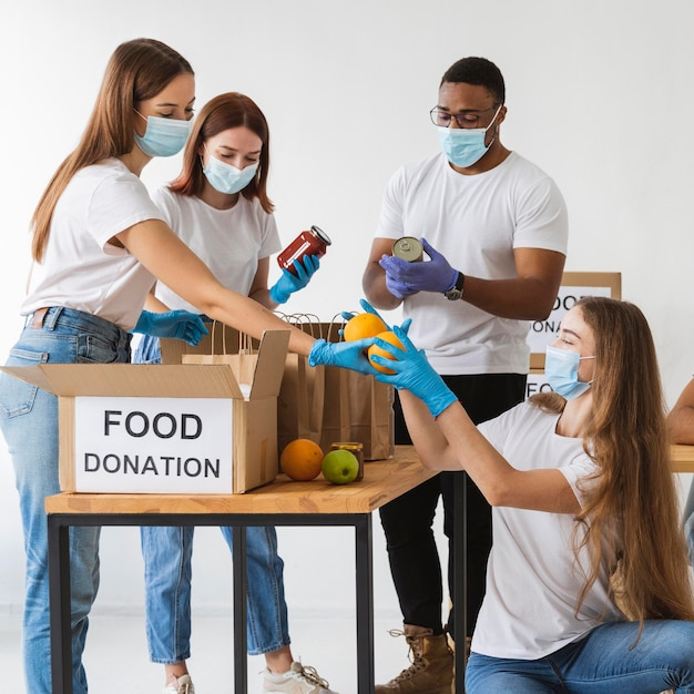 Volunteers with medical masks preparing donation boxes Free Photo