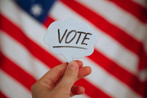 Слово голосования на американском флаге. концепция выборов Premium Фотографии