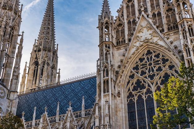 Votivkirche знаменитый готический фасад церкви и голубое небо в вене, австрия Premium Фотографии