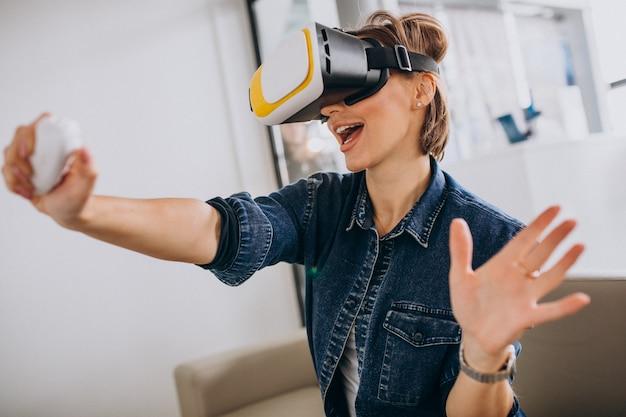 Молодая женщина в очках vr и играть в виртуальную игру, используя пульт Бесплатные Фотографии