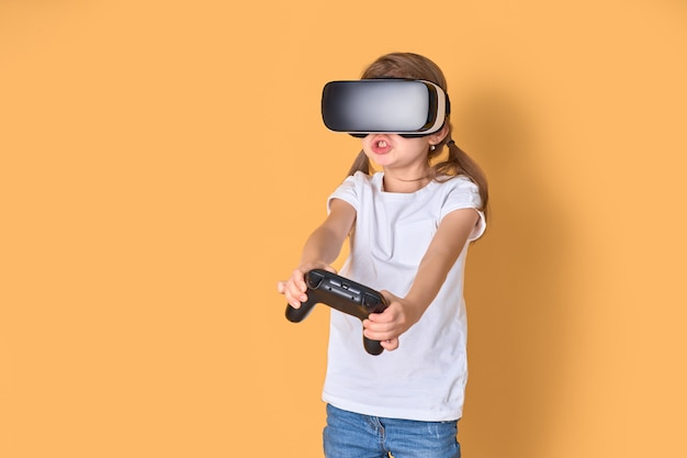 Vrヘッドセットとジョイスティックゲームを経験している少女。彼女の顔に驚いた感情。バーチャルリアリティにゲームガジェットを使用する子供。 Premium写真