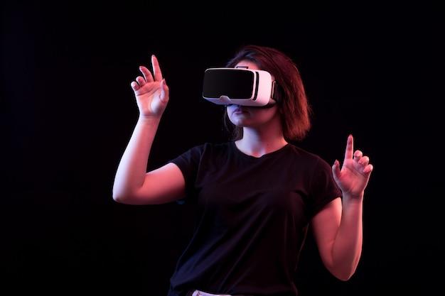 Вид спереди молодая красивая дама в черной футболке, одетый, играя vr развлечения игры на черном фоне Бесплатные Фотографии