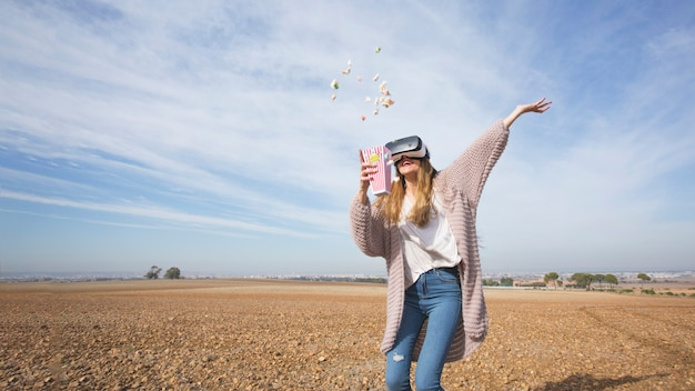 ポップコーンを投げているvrゴーグルの遊び心のある女性 無料写真