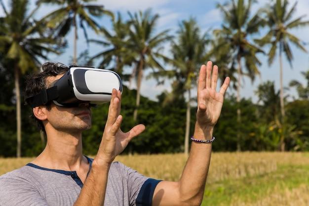 熱帯の田んぼでvrメガネの若い男 Premium写真