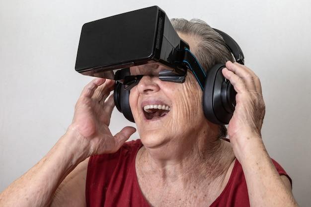 幸せな祖母は白い背景の上に現代のvrゴーグルガラスを使用します。新しいトレンドと技術コンセプトと面白い現役高齢者。 Premium写真