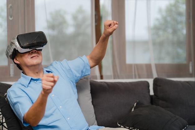 アジアの年配の男性は家でゲームをします。アジアシニア古い中国人男性の幸せな楽しさと仮想現実、ホームコンセプトのリビングルームでソファに横たわっている間ゲームをプレイするvr。 無料写真