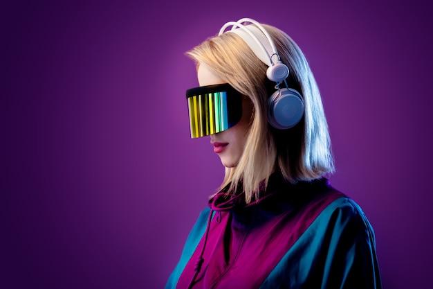 Блондинка в очках vr и наушниках на розовой стене Premium Фотографии