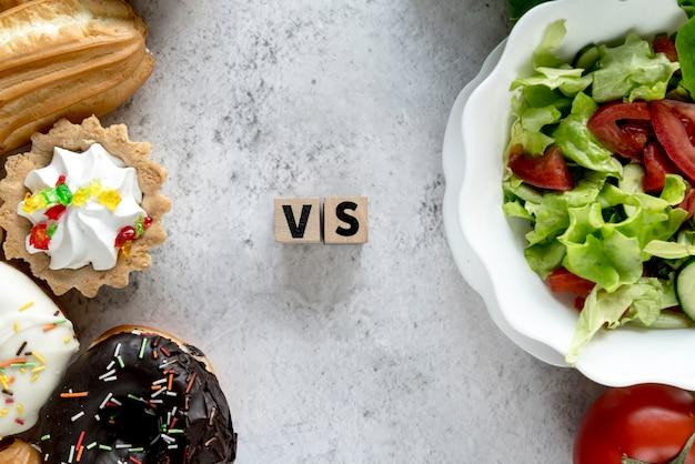 コンクリート背景に健康vs不健康な食べ物のハイアングル 無料写真