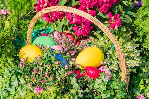 イースター通りの装飾。塗装イースターエッグ、ケーキ、花でいっぱいのwのバスケット。 Premium写真
