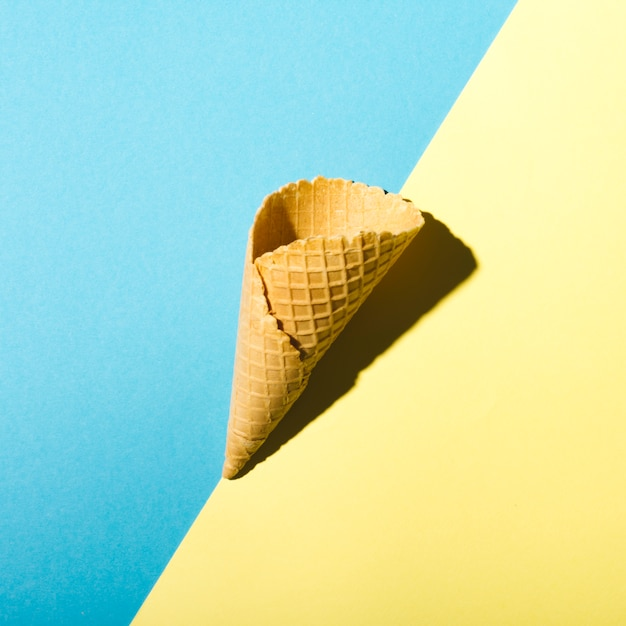 Waffle cone on blue and yellow background Free Photo