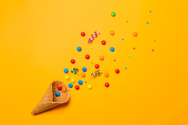 Waffle cone spilled from gems; sprinkles and streamers on yellow background Free Photo