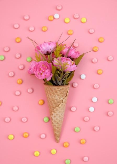 花とピンクの背景にカラフルなキャンディワッフルコーン Premium写真