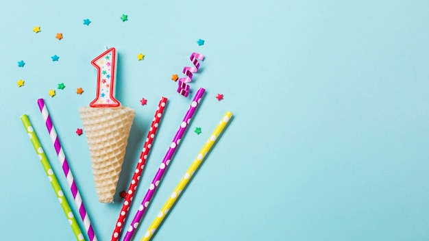 Waffle cone with number one candle; streamer and drinking straws on blue background Free Photo