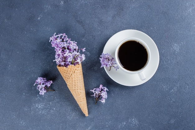 Waffle cone with purple lilac and cup of black coffee on dark blue stone concrete table background. Premium Photo