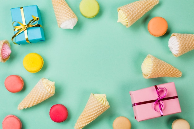 Waffle cones; macaroons and wrapped gift boxes on mint green backdrop Free Photo
