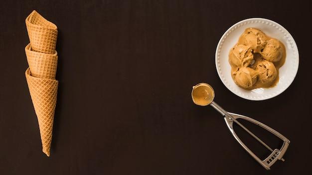 Waffle cones near ice cream balls on dish and scoop Free Photo