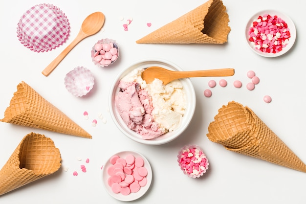 Waffle cones near ice cream on plate and sprinkles Free Photo