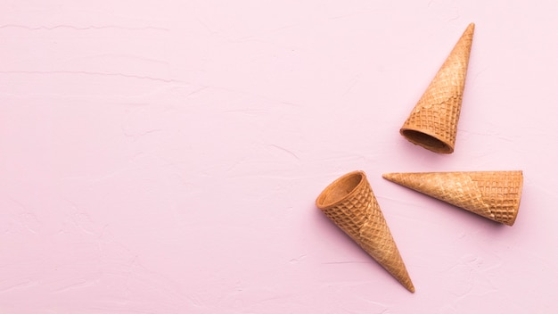 Waffle cones on pink texture background Free Photo