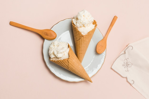 Waffle cones with ice cream and spoons on plate Free Photo