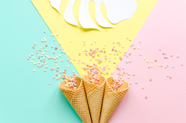 Waffle cones with sugar sprinkles and palm leaf Free Photo