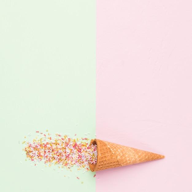 Waffle style sugar cone and rainbow sprinkles Free Photo