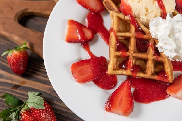 Waffle with strawberries, vanilla ice cream and whipped cream Free Photo