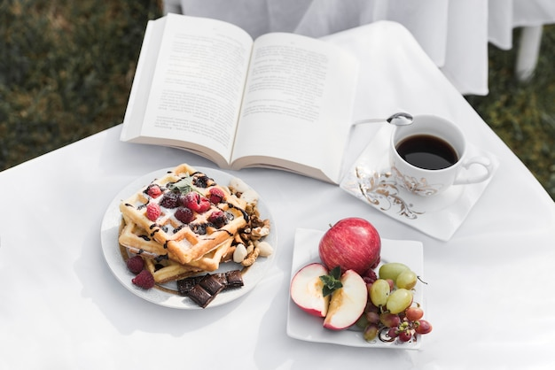 Waffles; fruits; coffee cup and an open book on white table Free Photo