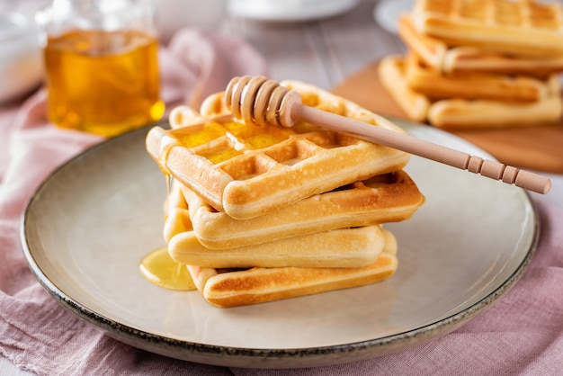 Waffles with honey on a light background Premium Photo