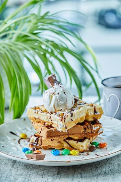 Cialde con gelato, cioccolato, palline di cioccolato sulla piastra bianca con tè Foto Gratuite