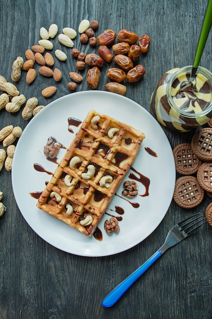 Waffles with nuts and chocolate paste for breakfast Premium Photo