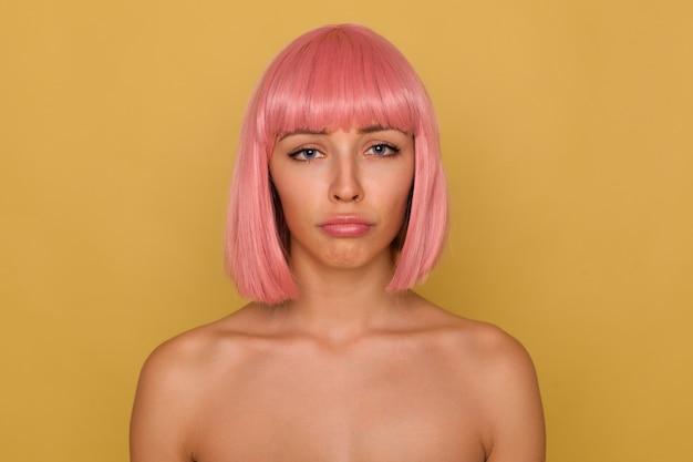짧은 머리가 슬프게도 카메라를보고 벌거 벗은 어깨와 함께 겨자 벽 위에 서있는 동안 그녀의 입술을 삐죽 삐죽 삐죽 삐죽 한 젊은 매력적인 분홍색 머리 여성 무료 사진