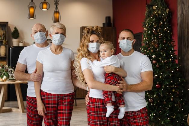 Талия большой семьи в пижаме и защитных масках, стоящая в гостиной в канун рождества Premium Фотографии