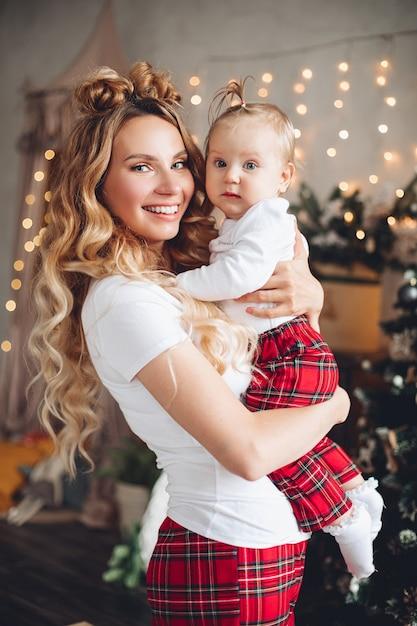 Талия счастливая мать с ее милым ребенком позирует в канун рождества Premium Фотографии