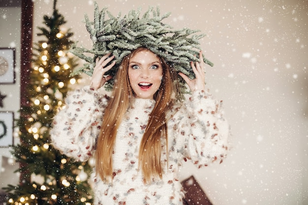 Foto della vita di una signora dai capelli rossi eccitata che indossa una corona di rami di abete in uno sciame di fiocchi di neve Foto Gratuite