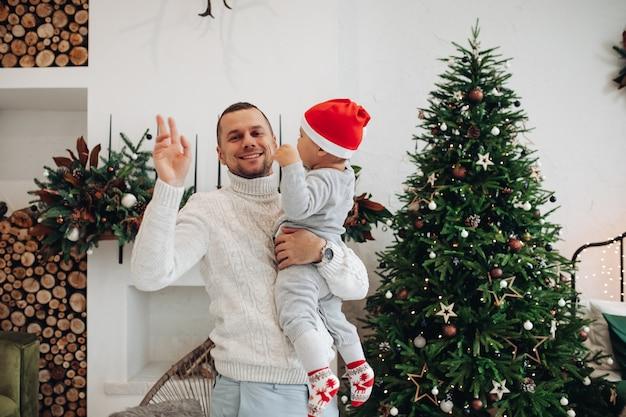 クリスマスツリーの近くで子供を振って抱きしめて幸せなお父さんのウエストアップ写真 無料写真