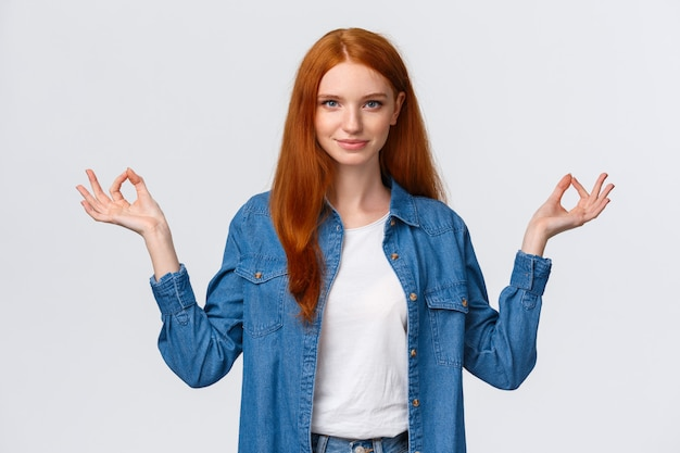 Waist-up portrait confident and relieved, patient good-looking redhead woman calm down daily yoga practice with app, hold hands sideways zen gesture in lotus pose, look assertive Premium Photo