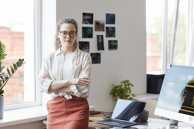 Waist up portrait of creative young woman looking at camera while standing with arms crossed by desk in modern office interior, copy space Premium Photo