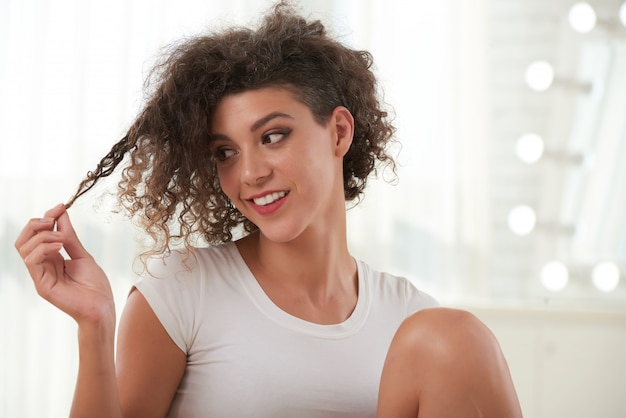 Waist up portrait of curly lady playing with her hair Free Photo