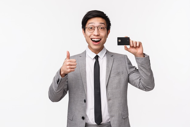 Waist-up portrait of excited, happy smiling asian male office worker, employee in grey suit and glasses, showing credit card and make thumbs-up sign, recommend bank, on a white wall Premium Photo