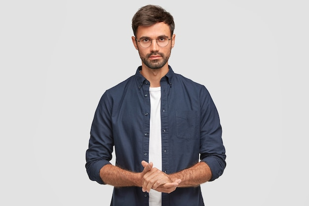 Waist up portrait of handsome serious unshaven male keeps hands together, dressed in dark blue shirt, has talk with interlocutor, stands against white wall. self confident man freelancer Free Photo