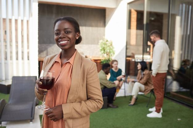 Талия вверх портрет элегантной афроамериканской женщины, держащей бокал и наслаждающейся вечеринкой на открытом воздухе, Premium Фотографии
